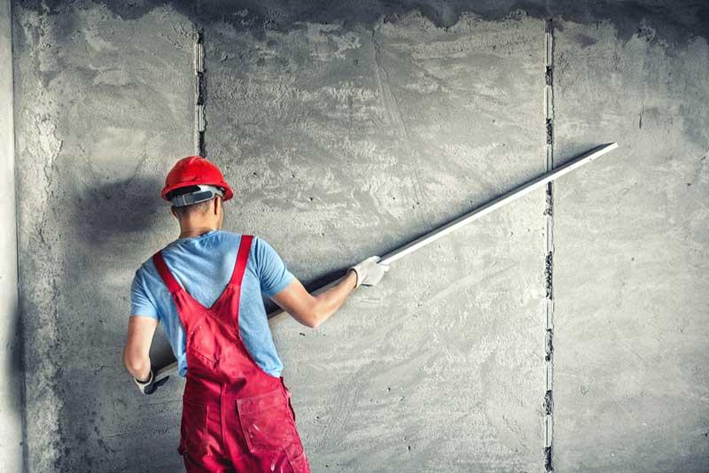 Een goedkope stucadoor een muur aan het glad strijken
